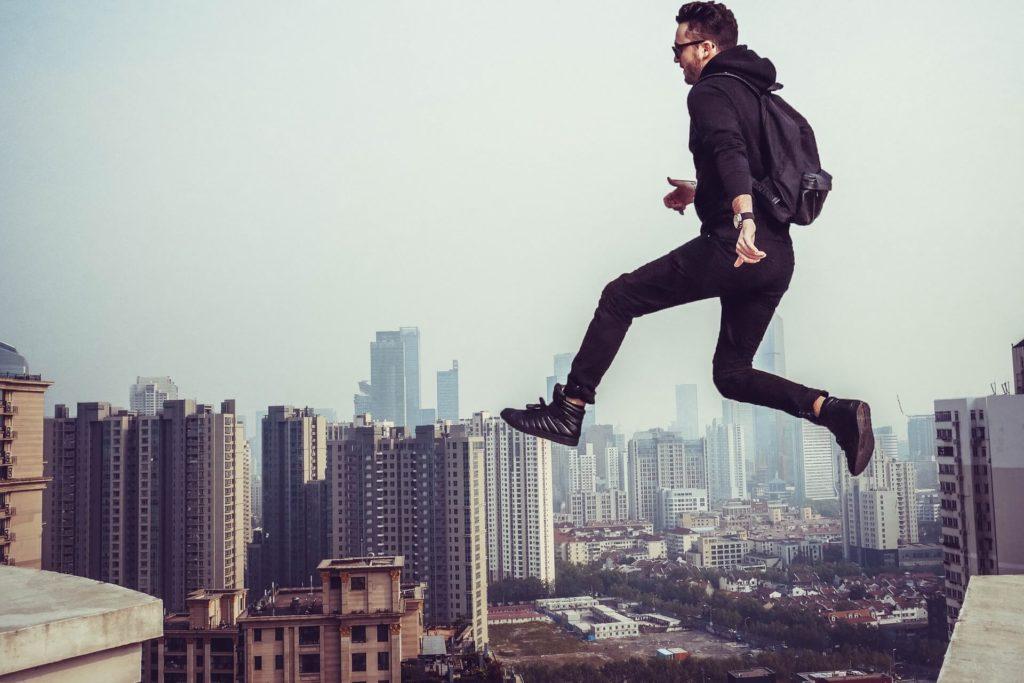 Mann springt von einem Gebäude auf ein anderes. Symbolisiert: Gründer müssen einen mutigen Schritt machen.