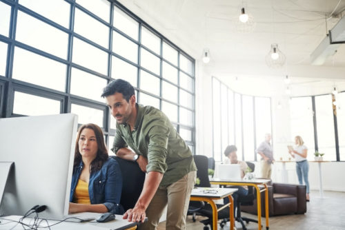 Ein Mann und eine Frau machen sich im Büro Gedanken und schauen auf einen PC-Monitor