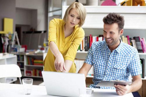 Freiberufler-Versicherung: Zwei Freiberufler beraten sich an einem Laptop