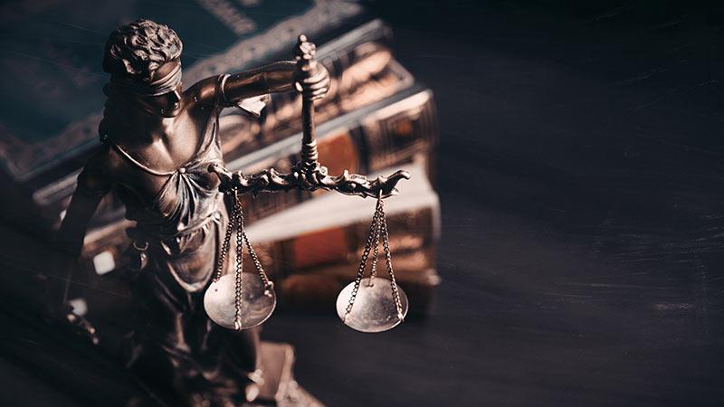 Justitia steht vor Gesetzbüchern